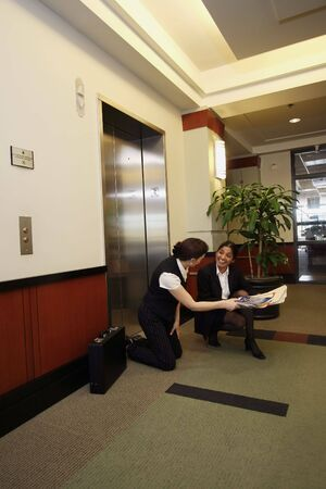 good samaritan: A female businesswoman helping another pick up some files she dropped on the floor outside the elevator