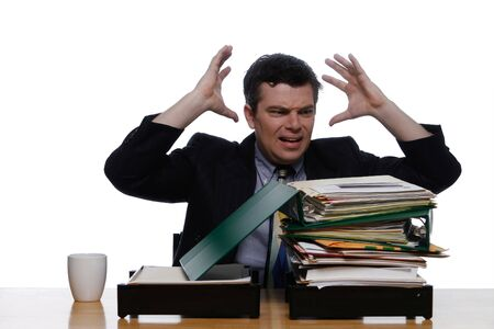 An isolated shot, on white, of a businessman looking at a stack of paper work.  Hes visibly losing his composure.