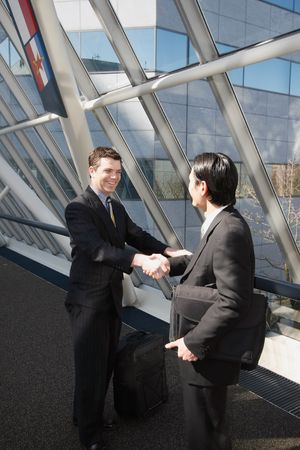 Two businessmen smiling and shaking hands in an office lobby photo