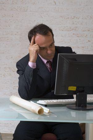 Un coup isolé d'un homme d'affaires regardant un ordinateur, avec sa main droite sur la tête, à la recherche complètement perdu dans ses pensées. Banque d'images - 3020017