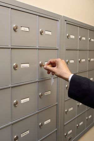 Close up of a hand putting a key into a lock in a row of mailboxes or safety deposit boxes