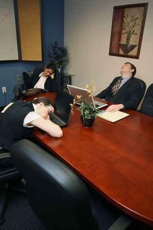 Team of colleagues fast asleep in a meeting room photo