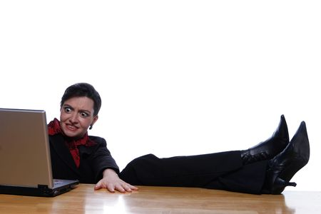 disbelief: An isolated shot, on white, of a businesswoman using computer with her feet up on the desk.  Her face is showing the expression of disbelief or surprise. Stock Photo