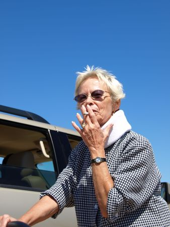 Older woman with close-cropped white hair taking a drag from a cigarette while standing outside in the desert. Shot is framed against a clear blue sky and desert sand.