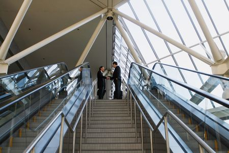 Panoramic shot of two businessmen shaking hands at the top of a stairway Stock Photo