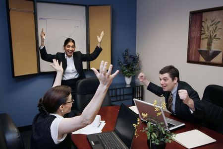 Team of three work colleagues with their arms raised in celebration Stock Photo