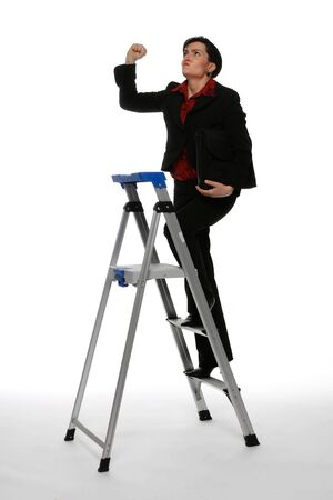 prejudice: Businesswoman climbing a stepladder with an angry expression on her face shaking her fist at the ceiling
