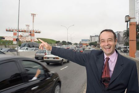flagging: A shot of a businessman flagging down a taxi.