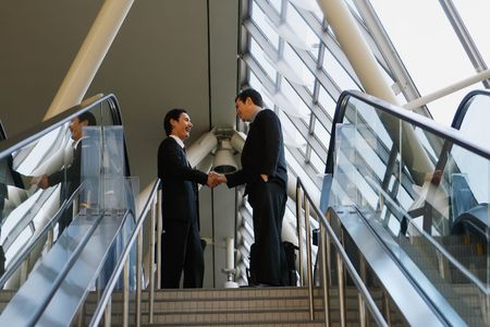 Two businessmen shaking hands at the top of a stairway