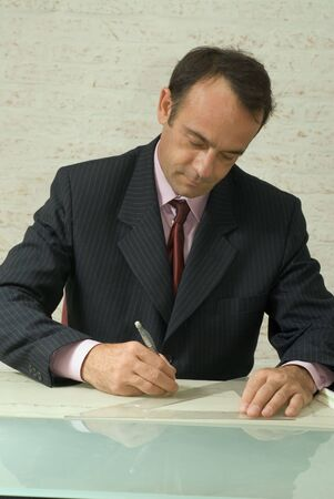 An isolated shot of a businessman  architect drawing blueprints using a protractor. photo