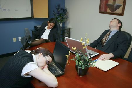 Team of colleagues fast asleep in a meeting room