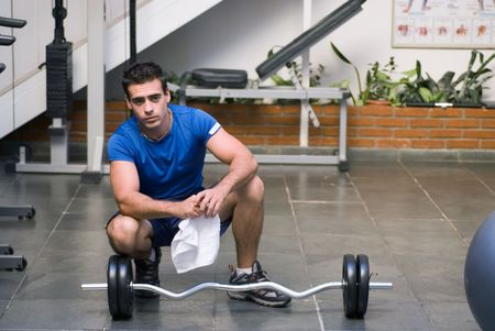 Young male athlete taking a break from lifting and wiping his head with a towel during a workout at the gym