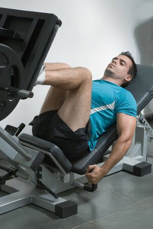 An isolated shot of a male weightlifter using a leg press machine. 版權商用圖片