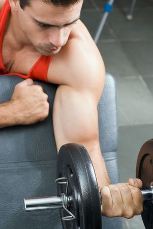 A shot of a male weightlifter doing a bicep curl with a barbell. photo