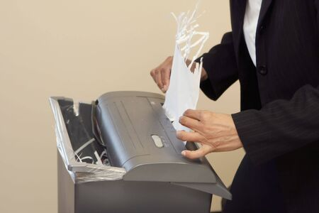 subpoena: Close-up of a woman shredding a piece of paper in an office shredder