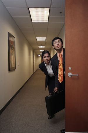 A shot of a businessman and businesswoman sneaking out of an office. Both looking in the same direction.