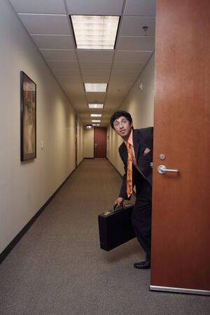 corporate espionage: Businessman looking around suspiciously with his briefcase in hand in an empty hallway