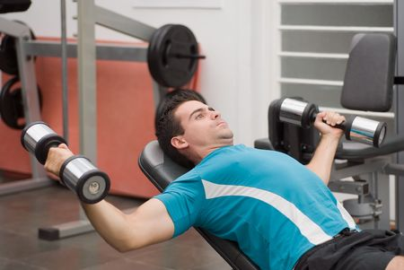pectorals: Young, athletic man in the gym doing a chest press on a weight bench