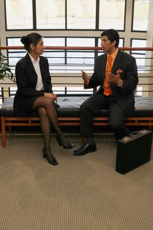 A shot of a businessman and businesswoman sitting on bench in lobby having a coversation. photo