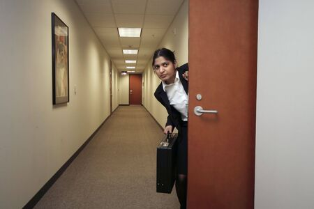 corporate espionage: Businesswoman looking around suspiciously with her briefcase in hand in an empty hallway