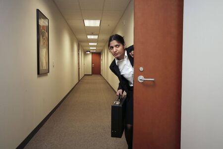looking around: Businesswoman looking around suspiciously with her briefcase in hand in an empty hallway