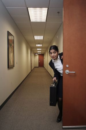 sneaking: Businesswoman looking around suspiciously with a briefcase in hand in an empty hallway Stock Photo