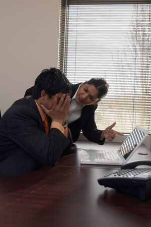 subordinate: Female boss reprimanding a subordinate while pointing her finger at his computer screen