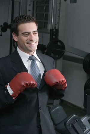 Confident attractive man in a business suit and wearing boxing gloves. Shot is set in a gym and he has a big smile on his face photo