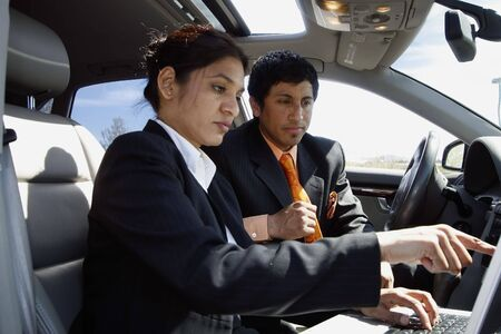 Business colleagues reviewing something on a laptop while seated in a car on a sunny day