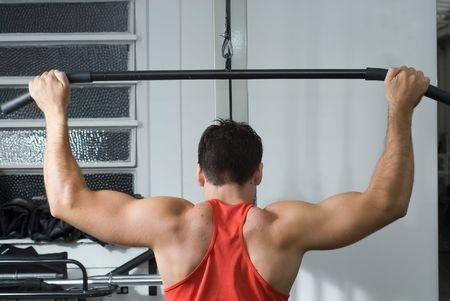 latissimus: Shot della muscolatura posteriore di un atleta di sesso maschile di lavoro su un lat pull-down macchina si frequenta la palestra,