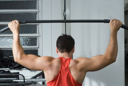 chiseled: Shot of the muscular back of a male athlete working out on a lat pull-down machine at the gym