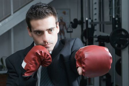 Handsome young businessman throwing a punch while standing in a gym and wearing boxing gloves photo