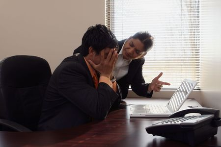 subordinate: Female boss dressing down a younger male subordinate while pointing a finger at his laptop screen