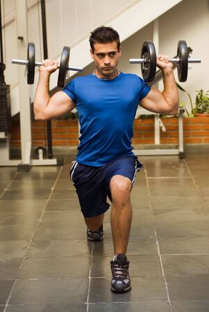 lunges: Athletic, attractive man doing lunges with dumbbells in a gym