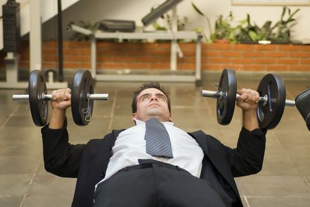 Athletic, young businessman bench pressing weights in a gym