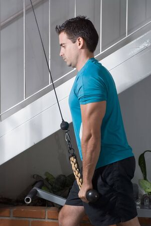tricep: Male athelete doing tricep pulldowns Stock Photo