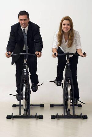 男性と女性のビジネス部門の同僚はエアロバイクに乗っている間前方に直面しています。垂直方向にフレーム - ショットを分離しました。 写真素材