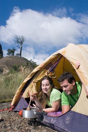 Attractive young couple cooking a meal in their tent. Shot is framed against a beautiful blue sky photo