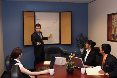 A shot of a businessman presenting in front of two businesswomen and one businessman.  His looking at the audince while pointing at the whiteboard with a banana. Stock Photo