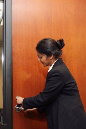 locking: Businesswoman locking a door.