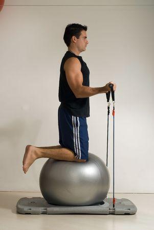 poleas: Athletic, guapo hombre haciendo ejercicios con una pelota botando y el�stica poleas. Aislada