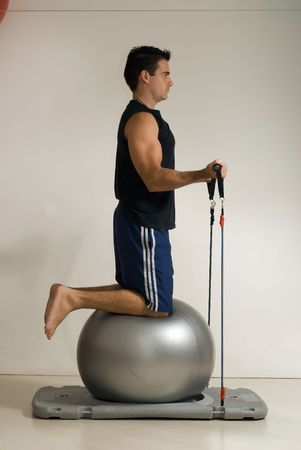 pulleys: Athletic, handsome man doing exercises with a bouncing ball and elastic pulleys. Isolated