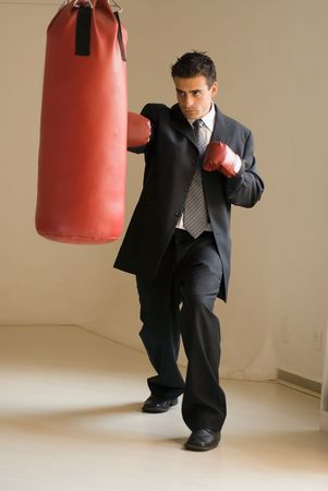 jab: Young attractive businessman throwing a jab at a heavy punching bag