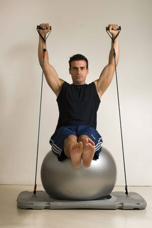 vertically: Vertically framed shot shot of a young athletic man doing Pilates on a balance ball. Isolated against a gray studio background
