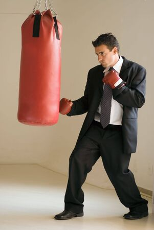 Young attractive businessman throwing a punch at a heavy punching bag