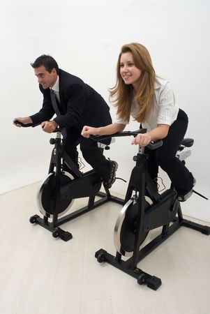 Zoomed out vertically composed shot of two businesspeople (male and female) working out on exercise bikes. Isolated