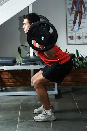 Athlete doing squats with a barbell.