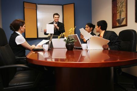 boardroom meeting: Businessman presenting to two businesswomen and one businessman.  The presenter is holding a piece of paper and smiling. Stock Photo
