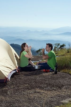 Young attractive couple enjoying a glass of wine with their open air meal. Vertically framed shot. photo