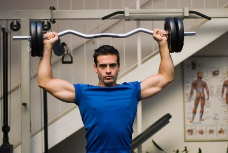 Fit, attractive man lifting a barbell over his head (overhead press) in a gym